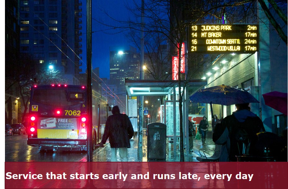 dark city street in the rain with a lit up covered RapidRide Bus Station and light up screen with live bus times updating.