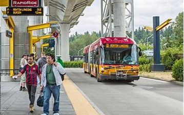 RapidRide bus with wheels pulling into a station with real-time arrival signs. A few people are waiting at the station. RapidRide buses include several upgrades like all-door boarding, more frequent service, the ability for riders mobility aids to secure themselves easily, etc.