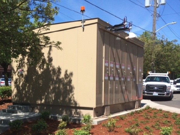 A photo of a traction power substation; a tan colored square metal structure approximately 13 by 21 feet that's installed a few feet back from the sidewalk beneath a powerline